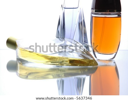 Perfume bottles product shot on reflective surface. - stock photo