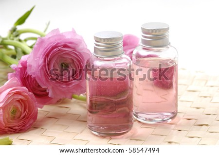 Perfume bottles with dahlia flower on woven mat