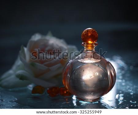 Perfume bottles with white rose - stock photo
