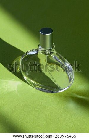 Perfume glass  bottle on green background