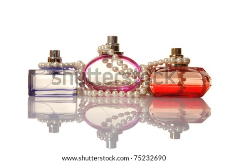 Perfume in a glass bottles and pearl beeds on white background - stock photo