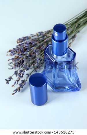 Perfume in bottle and lavender isolated on white