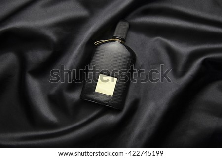 perfume on black abstract background luxury cloth - stock photo