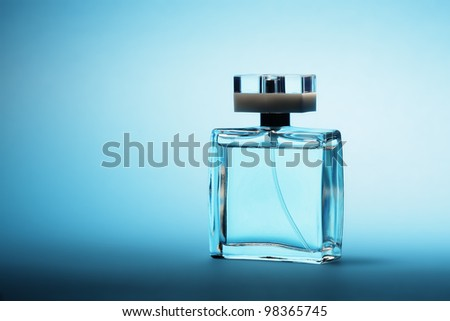Perfume on blue background - stock photo