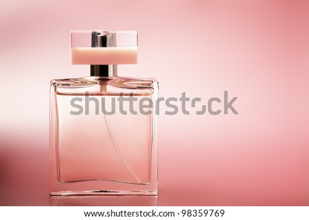 Perfume on pink background - stock photo