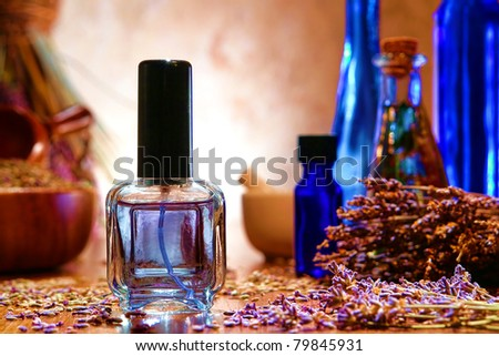 Perfume spray bottle filled with scented water and fresh lavender flowers with scattered seeds and blue bottles of natural essential oil in a traditional aromatherapy artisan shop - stock photo