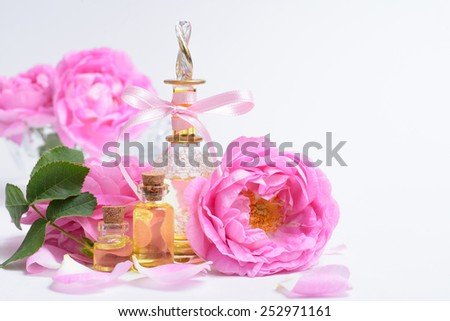 Perfumes in small bottles, decorated with tea roses - stock photo