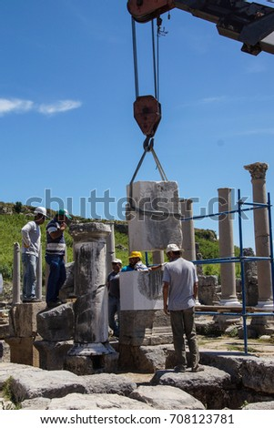 PERGE, TURKEY - JUN 2, 2014 - Works use modern equipment to restore ancient columns in  Perge,  Turkey
