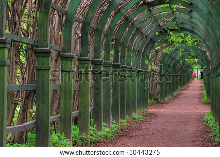 Pergola. Wooden arches and footpath escaping afar. - stock photo