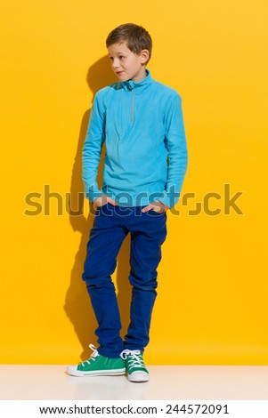 Perky boy. Young boy posing with hands in pockets. Full length length studio shot on yellow background. - stock photo