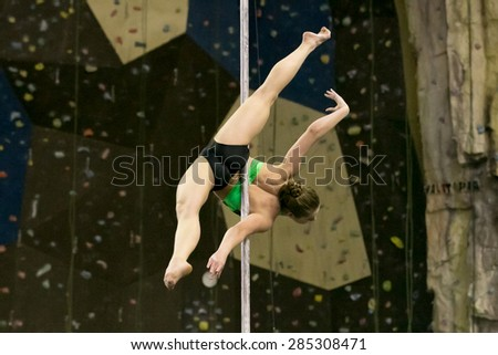 Perm, Russia - April 25, 2015. Championship Perm region at pole sport and dance.  Girl in a black swimsuit with a green pattern making element Allegra without hands - stock photo