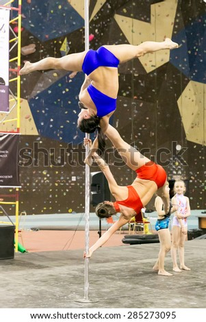 Perm, Russia - April 25, 2015. Championship Perm region at pole sport and dance. two girls in bright bathing suits make elements flag on one pole
