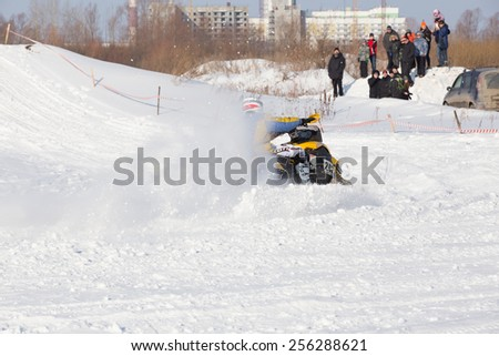 Perm, Russia - February 23, 2015. Championship on Cross Country Snowmobile. Racer on black snowmobile raises clouds of snow near hill