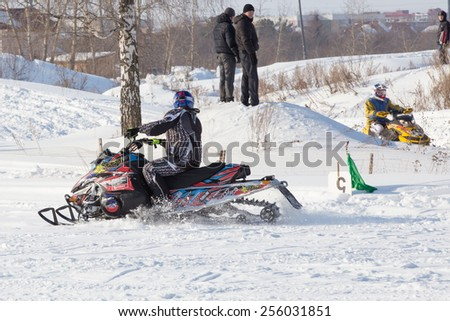 Perm, Russia - February 23, 2015. Championship on Cross Country Snowmobiles. Rider on a black snowmobile and viewers