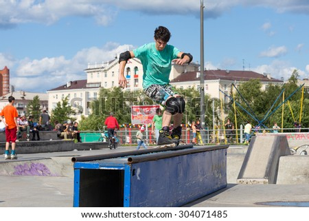 Perm, Russia - July 26, 2015. Free access to the Extreme Park in the city of Perm. teenager in green T-shirt and shorts does slip on the rollers on the rails sideways front view - stock photo