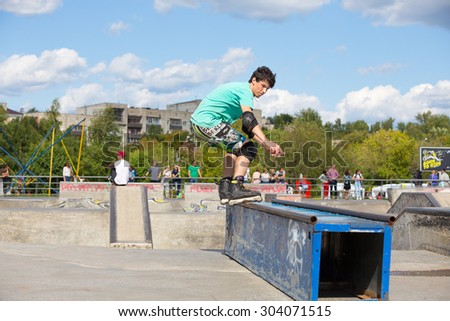 Perm, Russia - July 26, 2015. Free access to the Extreme Park in the city of Perm. teenager in green T-shirt and shorts does slip on the rollers on the rails sideways - stock photo
