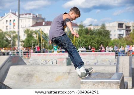 Perm, Russia - July 26, 2015. Free access to the Extreme Park in the city of Perm. young man in jeans and a gray tank top rides on the rails on the rollers sideways - stock photo