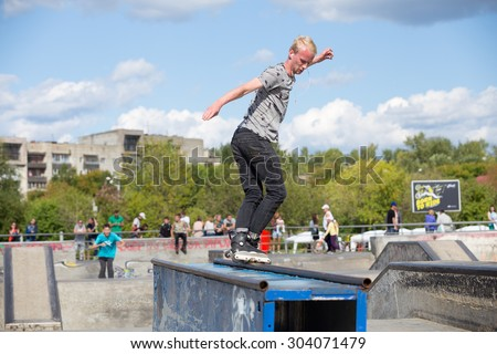 Perm, Russia - July 26, 2015. Free access to the Extreme Park in the city of Perm. young man on roller skate on the railing with his back legs crossed