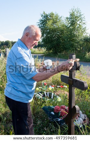 Perm, Russia - July 13.2016: Man paints a wooden cross on the cemetery