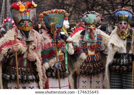 PERNIK, BULGARIA - JAN 25, 2014: Traditional Kukeri costume are seen at the the International Festival of the Masquerade Games Surva in Pernik, Bulgaria. Photo taken on: January 25th, 2014  - stock photo