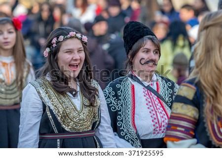 PERNIK, BULGARIA - JANUARY 30, 2016: A girl in a traditional regional folklore costume is laughing and having fun at Surva, the International Festival of the Masquerade Games