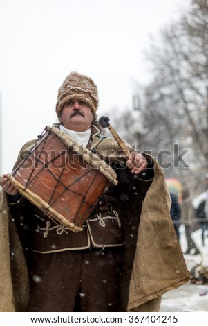 "PERNIK, BULGARIA - JANUARY 26, 2014: Man with mustaches playing on a big drum  during a traditional Bulgarian festival for banishing evil spirits called ""Surva""."