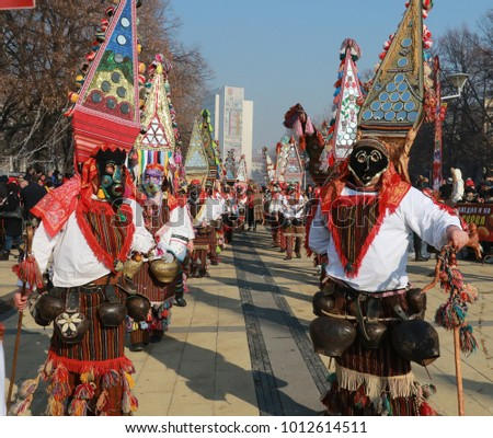 Pernik, Bulgaria - January 28, 2018: People with mask called Kukeri dance and perform to scare the evil spirits at the International Festival of Masquerade Games Surva in town Pernik, Bulgaria.