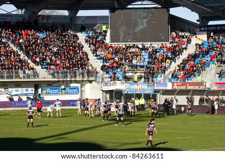PERPIGNAN - JANUARY 2: Supporters and players during the Rugby Top14 French Championship match between USAP Perpignan (blue) and Brive, final score 23 - 16, on January 2, 2011 in Perpignan, France.