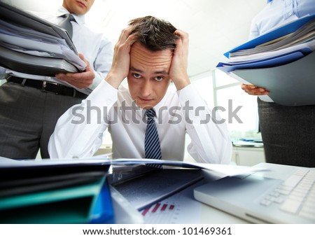 Perplexed accountant touching his head being surrounded by business partners with huge piles of documents - stock photo