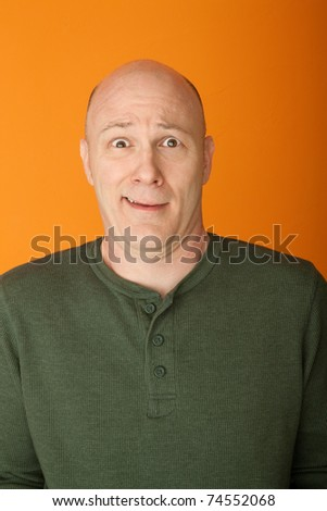 Perplexed bald middle-aged Caucasian man on orange background - stock photo