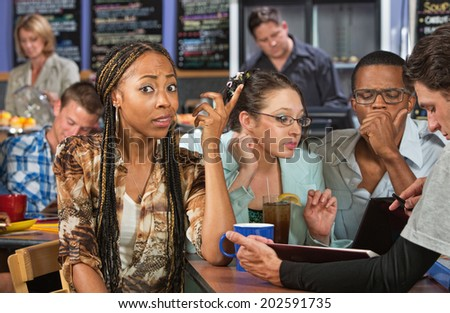 Perplexed beautiful African student studying with friends - stock photo