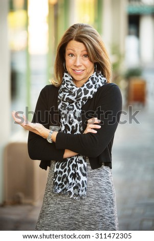 Perplexed businesswoman with folded arms standing in urban scene