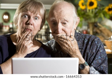 Perplexed Senior Couple in their Dining Room with a Laptop Computer - stock photo