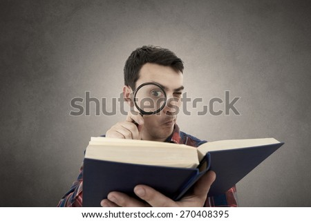 Perplexed Young man student holding magnifying glass and a book isolated over grey background.Curious young student man holding book with a magnifying glass. - stock photo