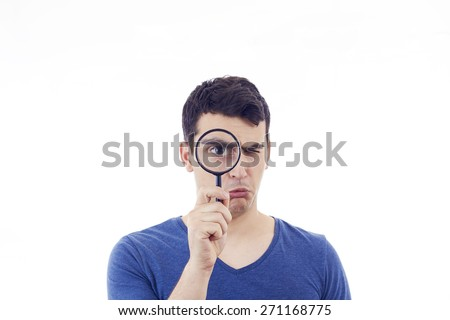 Perplexed Young man student holding magnifying glass isolated over grey background.