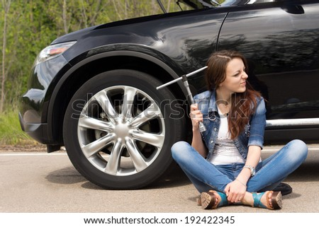 Perplexed young woman waiting for roadside assistance after her car breaks down at the side of the road sitting holding the wheel spanner and grimacing - stock photo