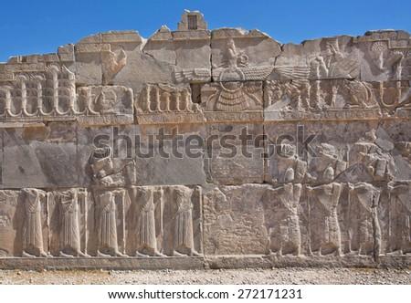 PERSEPOLIS, IRAN - OCT 22: Scene with Faravahar - relief of winged sun symbol of Zoroastrianism in ruined Persepolis on October 22, 2014. Persepolis was a capital of Achaemenid Empire (550 - 330 BC) - stock photo