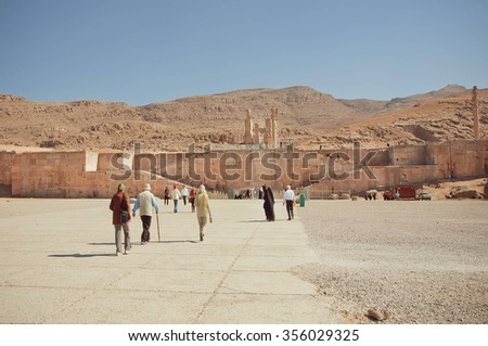 PERSEPOLIS, IRAN - OCT 22: Tourists walking to the great ruined Persepolis city in mountains on October 22, 2014. Persepolis was capital of Achaemenid Empire, 550 - 330 BC.  - stock photo