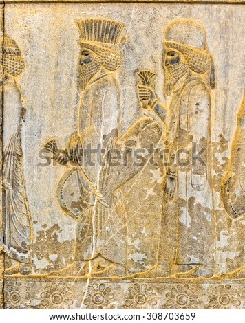 Persian noblemen on their way to the royal feast bas-relief detail on the stairway facade of the Apadana at the old city Persepolis.