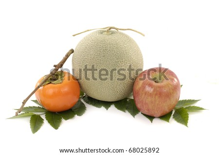 persimmon and melon, and apple on fruit leaf - stock photo