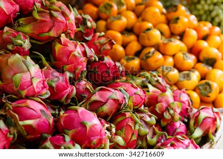 Persimmons and Dragon Fruit are stacked high at sidewalk market stall.