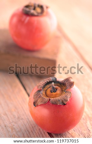 Persimmons on rustic wood - stock photo