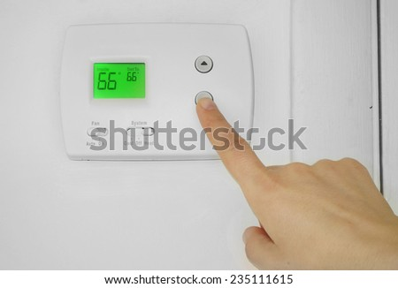 Person adjusting a wall thermostat temperature                                - stock photo