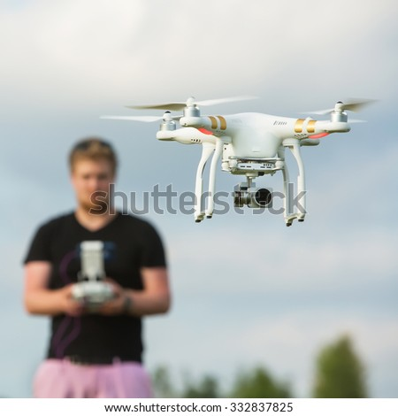 Person behind a surveillance camera with remote control - stock photo