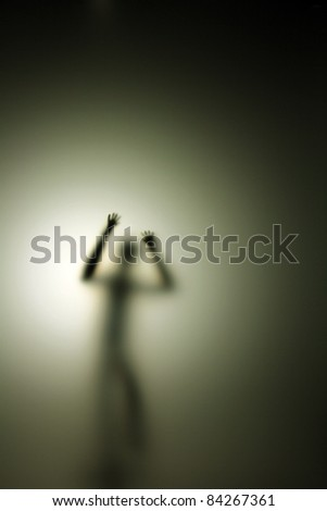 person behind glass in the back light - stock photo