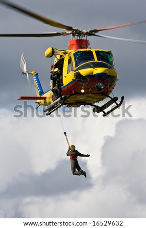 Person being winched up to an Air Sea Rescue helicopter - stock photo