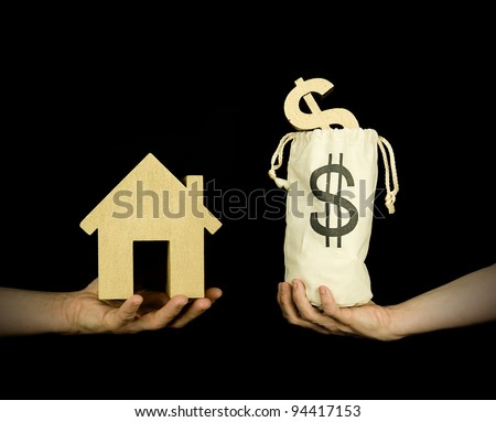 person buying a house with a bag full of dollars, black background - stock photo