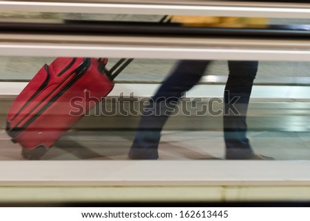 person carrying a suitcase on the conveyor belt in an airport terminal - stock photo