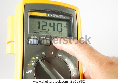 person changing settings on fluke digital meter. checking vehicle battery voltage - stock photo