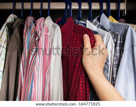 person chooses shirt in the closet of the multi-colored shirts - stock photo
